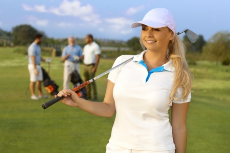 Portrait of pretty blonde female golfer with golf club, smiling, looking away. photo