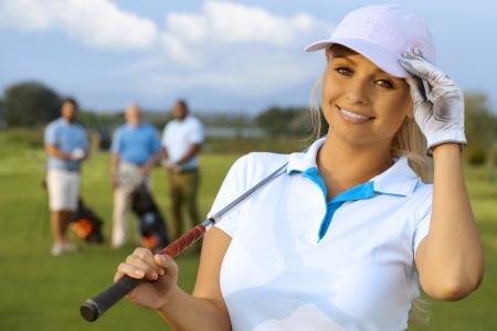 Retrato do close up do jogador de golfe feminino atraente nos campos, sorrindo, olhando a c
