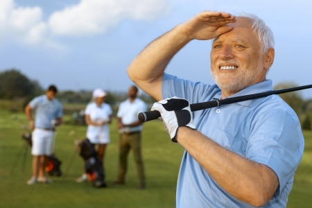 Closeup portrait of elderly male golfer, holding golf club, following shot. photo