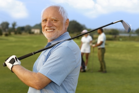 golfing: Close-up portret van volwassen mannelijke golfer bedrijf golfclub, lacht graag, camera kijken.