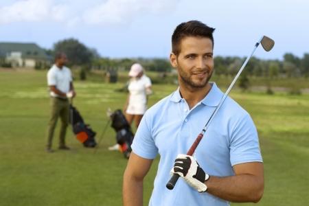 Outdoor ritratto di giovane giocatore di golf maschile holding golf club, sorridendo, guardando lontano. Archivio Fotografico - 25483558