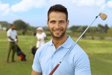 bel homme: Portrait de gros plan du beau jeune homme golfeur avec le club de golf.