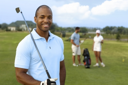 Closeup portrait of handsome young black golfer with golf club, smiling, looking at camera.