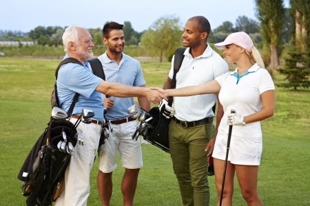 Golf partners shaking hands on the fields, smiling happy.