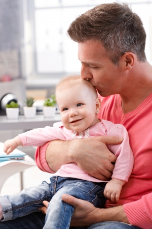 be kissed: Father sitting holding on lap baby daughter, kissing smiling babys head. Stock Photo