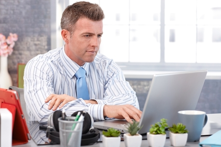 alone person: Businessman working with laptop, sitting at desk, typing on keyboard.