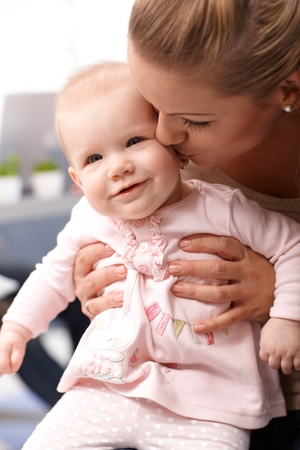 be kissed: Closeup photo of mother holding and kissing tender little baby daughter.
