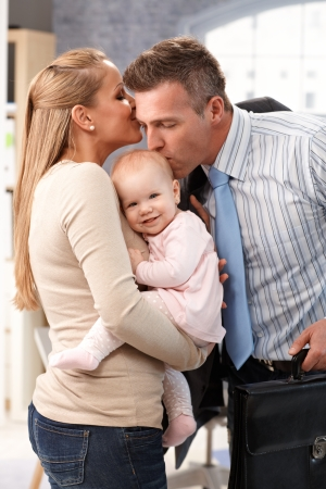 Businessman father arriving home from work, wife and little baby daughter greeting him with kiss.