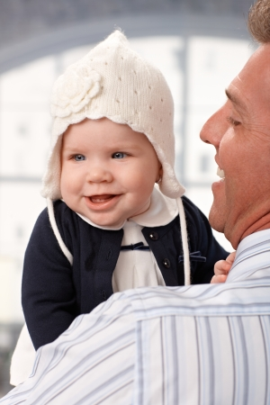 Closeup photo of happy baby girl in hat held by happy father. photo