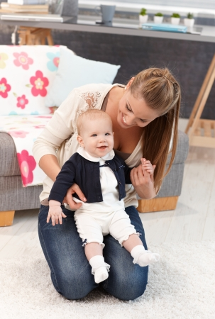Young mother kneeling on floor at home with little baby girl on lap. photo