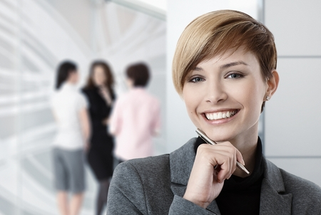 gingerish: Portrait of caucasian businesswoman at office, colleagues in background. Stock Photo