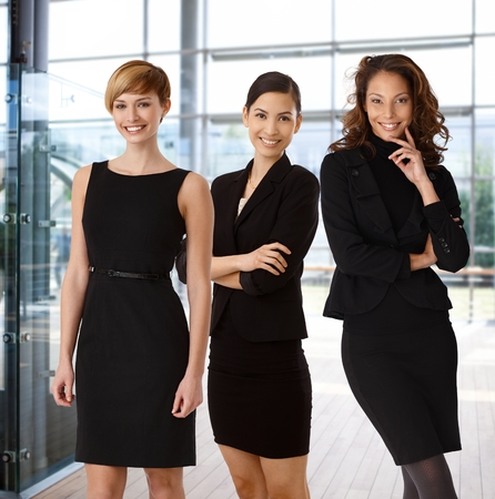 Interracial team of happy businesswomen at office lobby.