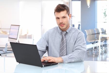 hombre sentado: Hombre de negocios cauc�sico joven en camisa y corbata, sentado en la oficina escritorio con ordenador port�til mirando a la c�mara. Foto de archivo