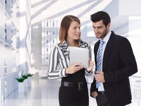 clothed: Formal clothed business partners holding tablet discussing at office, smiling.