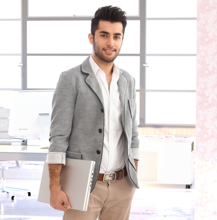 Portrait of modern young handsome arabian businessman at office, smiling. photo
