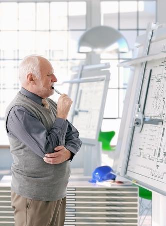 Architecte senior travaillant à bord de dessin, de penser.