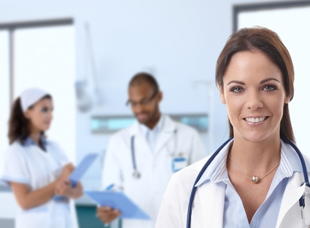 Caucasian female doctor at hospital looking at camera, smiling, medical staff working in background. Stock Photo - 25640694