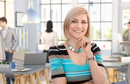 Happy casual caucasian woman standing at office, smiling, people working in background.