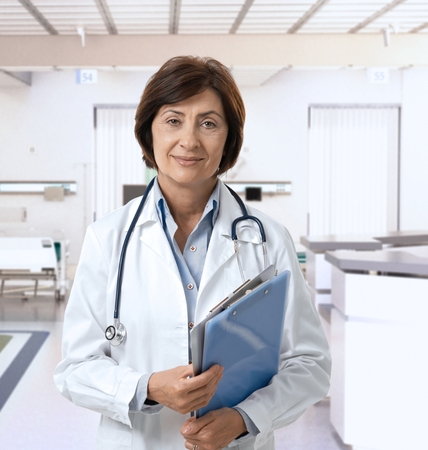 Friendly mature female doctor at hospital smiling. Standard-Bild