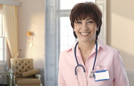 old age home: Senior nurse at elegant elite nursing-home smiling.