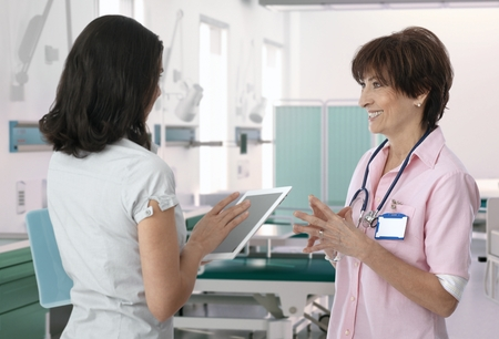 Medical staff talking using with tablet at hospital room.