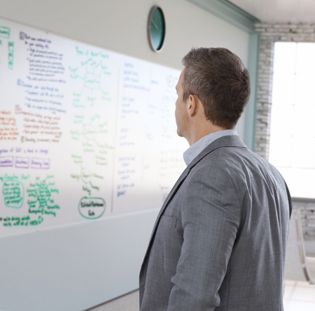 markerboard: Mid-adult caucasian businessman looking at plan on whiteboard, rear view.