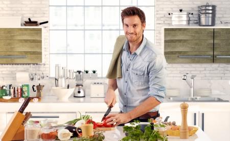 cooking eating: Hombre hermoso feliz cocina en cocina en casa. Foto de archivo