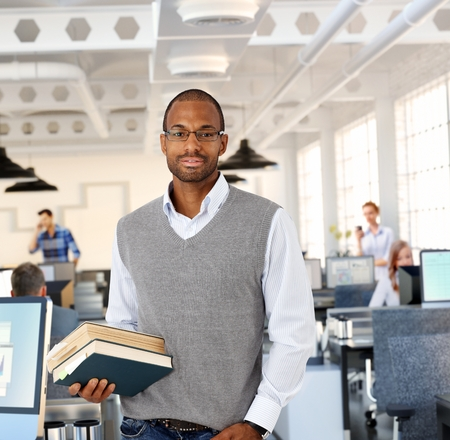 Intelligent black man at office holding books Stock Photo - 25608830