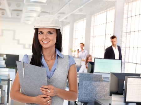 Happy trendy female office worker at busy workplace. Stock Photo - 25608832