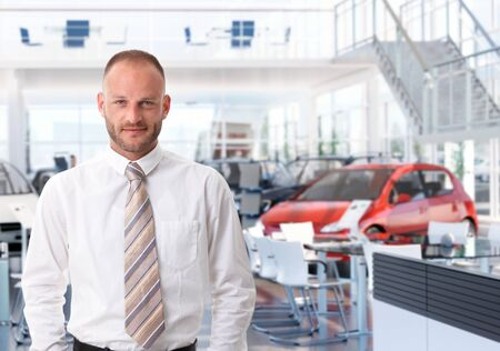 Portrait of car salesman in showroom, looking at camera, smiling. photo