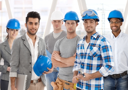 building industry: Group of diverse people from building industry: architects, managers, workers posing together for a team portrait. Stock Photo