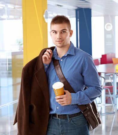 arriving: Young office worker arriving to modern office at morning holding coffee.