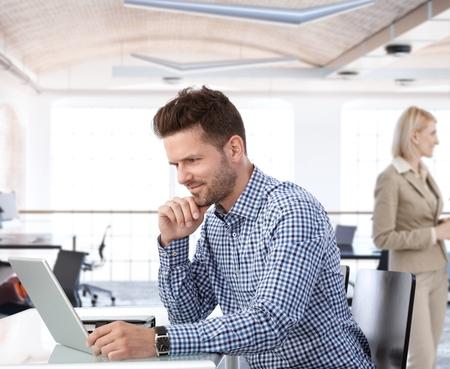business smile: Las personas que trabajan en la oficina, hombre de negocios usando la computadora port�til en el escritorio. Foto de archivo