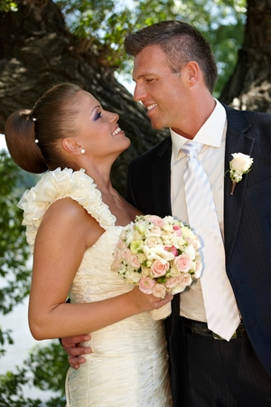 be kissed: Bride and groom kissing on wedding-day outdoors. Side view.
