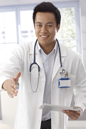 Happy young male doctor in lab coat holding tablet, giving hand for handshake. photo