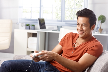 Young Asian man sitting in armchair at home, playing video game, smiing.