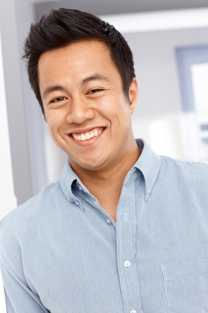 Close-up portrait of happy young Asian man, looking at camera. Stock Photo