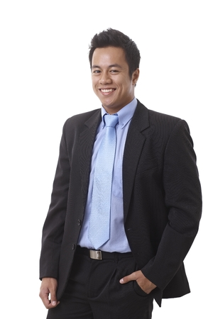 Young Asian businessman smiling with hand in pocket. photo