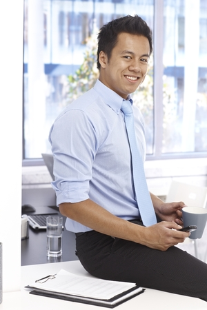 Young Asian businessman smiling as sitting on top of desk, holding mobilephone and tea mug. photo