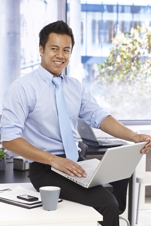 Happy young businessman using laptop computer in bright office, smiling, looking away. photo