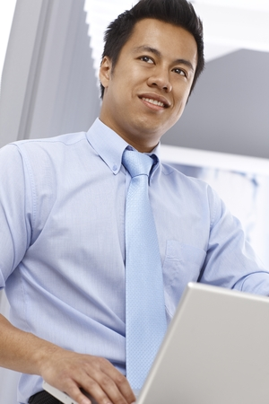 Young Asian businessman working with laptop computer, smiling, looking away. Below view.