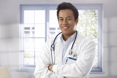 asian doctor: Portrait of happy young male doctor standing arms crossed, looking at camera.