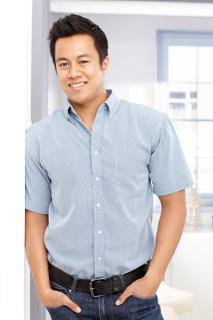 Portrait of handsome young Asian man standing against wall, smiling happy, looking at camera. photo