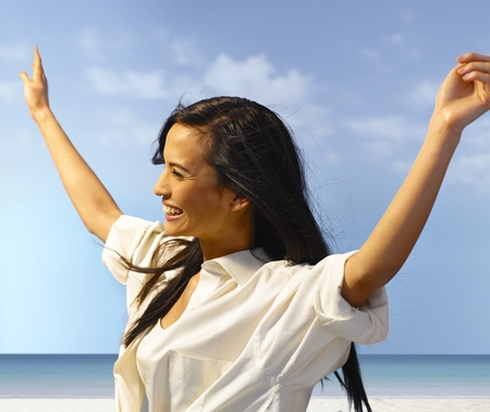outspreading: Attractive young woman enjoying summer holiday on the beach, laughing arms wide open.