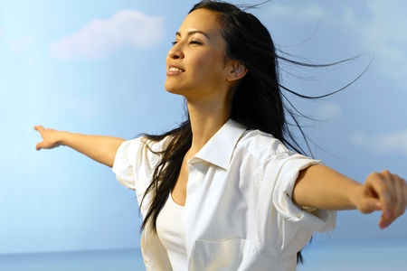 outspreading: Beautiful Asian woman enjoying summertime outdoors, flying with arms wide open.