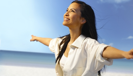 Beautiful Asian girl smiling happy on the beach, pretending to fly with arms wide open, enjoying freedom and sun. Standard-Bild