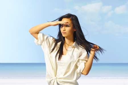 shading: Portrait of attractive young Asian girl on the beach, shading eyes by hand.