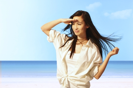 Summer portrait of beautiful young Asian woman on the beach smiling happy, shielding eyes by hand from sunshine. photo