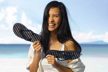Happy Asian woman laughing on the beach at summertime, holding flip flop in hand. photo