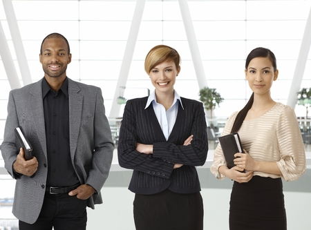 Interracial team of businesspeople standing for portrait in business hallway, smiling. Standard-Bild